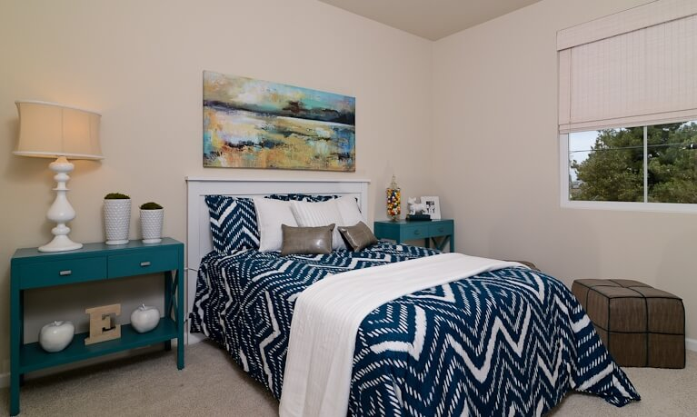 The master bedroom features a striking mixture of blues and white, with a pair of bold side tables flanking the bed. A large oil painting hangs above, while cubic ottoman sits below the window.