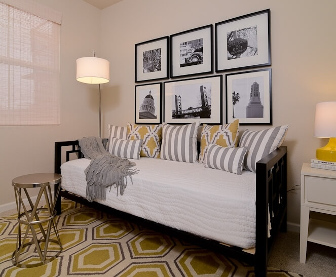 This daybed framed in deep black provides flexible seating or sleeping in the second bedroom, over a beehive pattern rug.