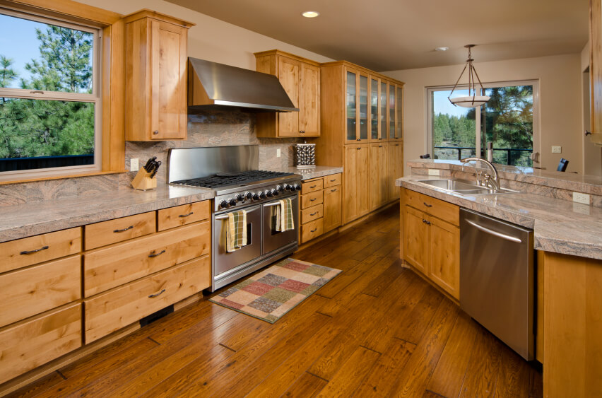 This lovely wooden kitchen has a dark hardwood floor that matches the beautiful colors in the cabinets and backsplash. The paint on the walls adds to the unified color scheme.