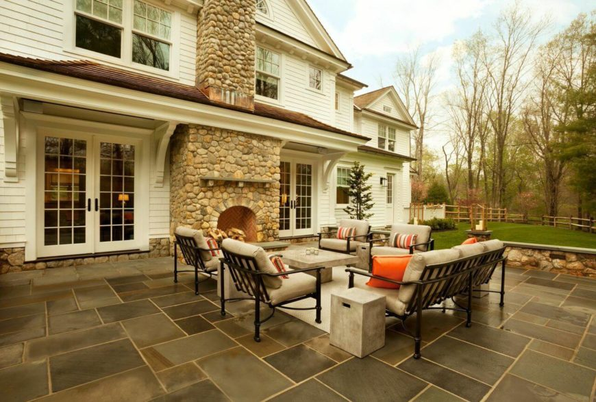 The home's backyard has an enormous stone patio with a wood-burning fireplace. Four chairs and a sofa are arranged around a concrete coffee table.