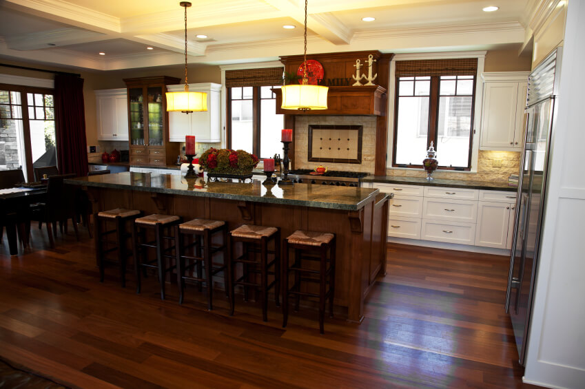 This quaint kitchen space has rich dark natural wooden floors with  breath-taking countertops and