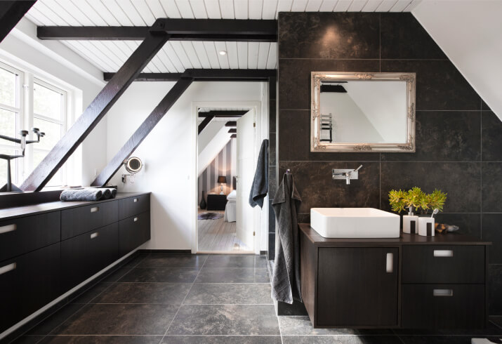 This upper-floor bathroom sports large format marble tile flooring beneath a host of natural wood, including the bespoke vanity at right and lengthy countertop and cabinetry at left. Exposed arched beams lead the way toward a bedroom.