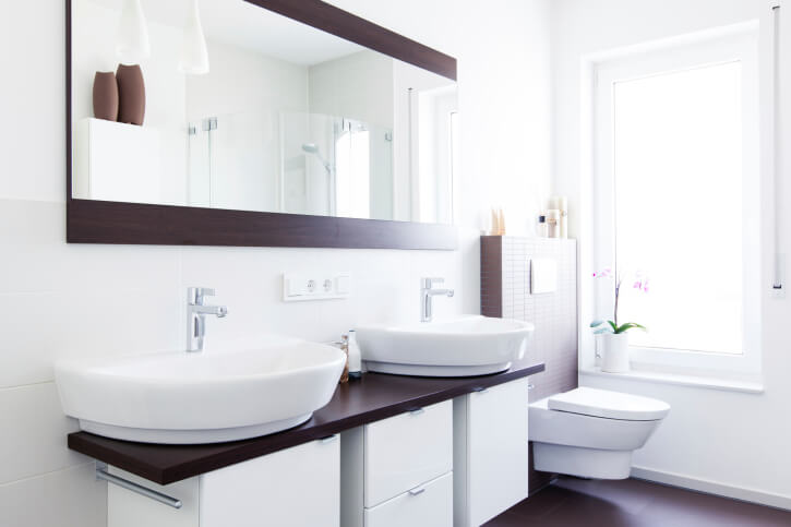 This Bright Bathroom Features A High Contrast Look With Dark Hardwood  Flooring, Countertop, And