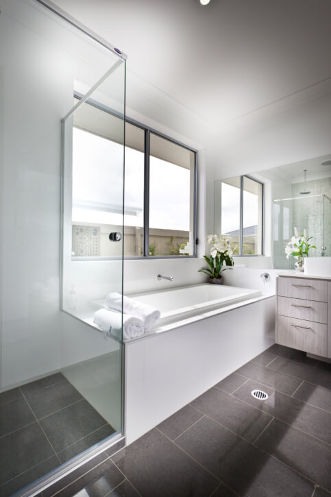 This Bright Bathroom Features Large Format Brown Tile Flooring And White  Walls And Bath Surround.