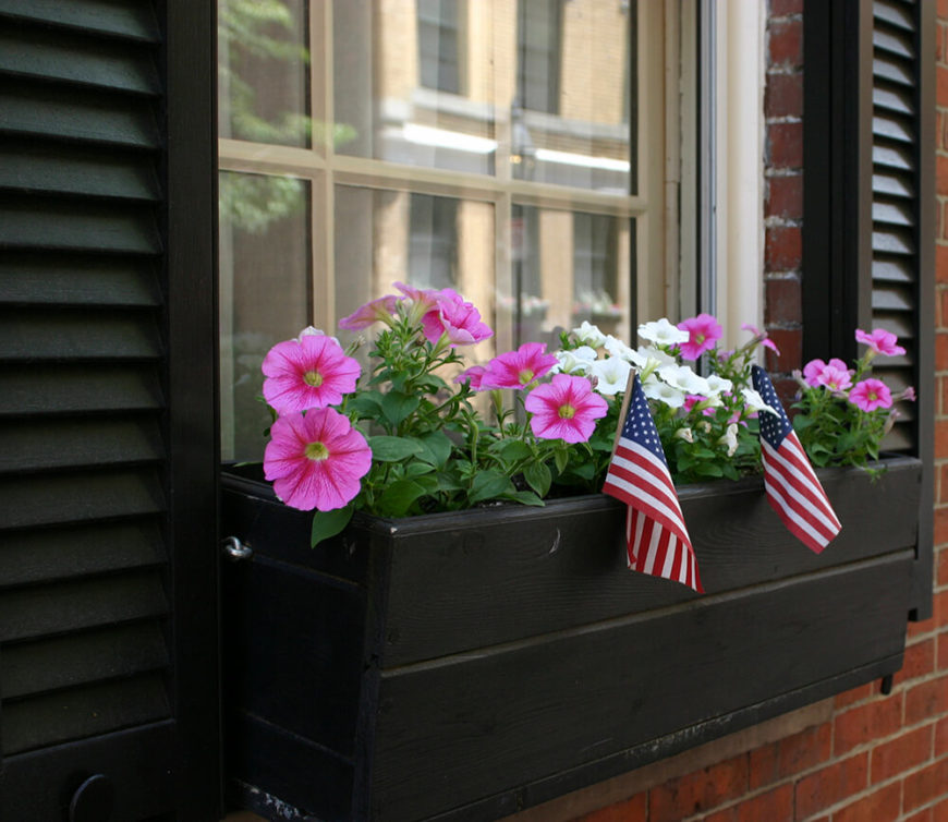 A simple wooden window box with pink and white petunias and two American flags for garnish.