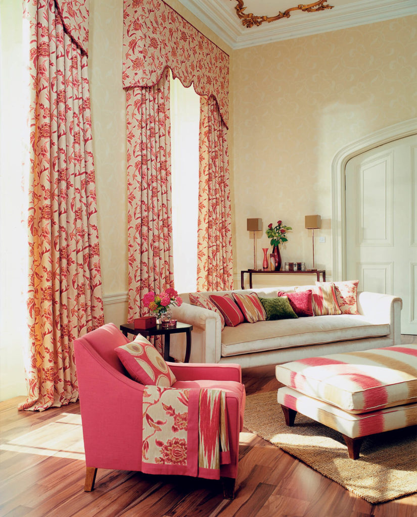 Floral curtains add an additional feminine touch to the light pink armchair, and accents throughout this room.