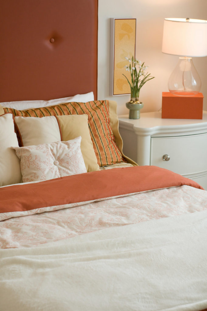 The deep peachy salmon splashes of color throughout this room offer a nice contrast against the blanch backdrop and furnishings. Striped accent pillows host a series of smaller neutral pillows, with a lovely white rectangular patterned piece in front.