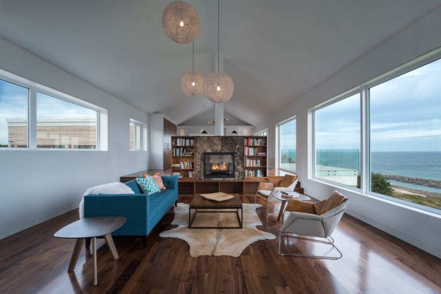 The long, narrow living room has beautiful hardwood floors and simple white walls that are covered in windows. To the rear of the frame is the marble enclosed fireplace with bookcases on either side.