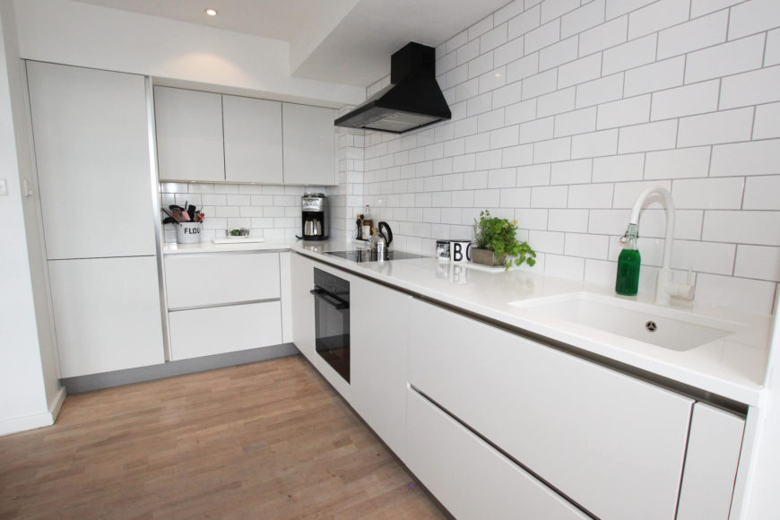 The subway tile backsplash complements the sleek countertops and hardware-less cupboards perfectly.