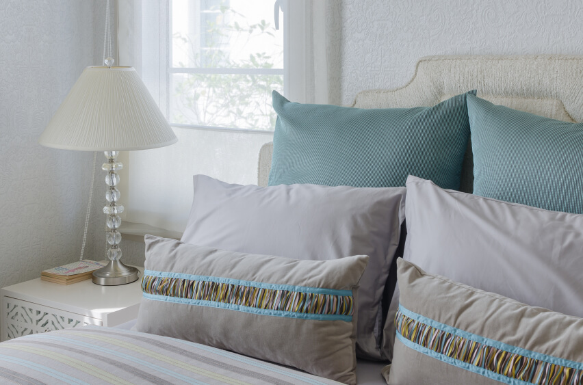 Soft grays and teals grace the ivory elegance of this quietly elegant bedroom.
