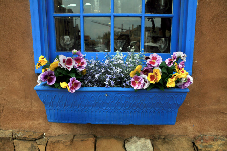 A bright blue window box with enormous pansy blooms in many different colors and smaller white blooms as well.