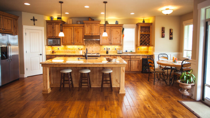 This superb kitchen has a golden glow of light hidden above and below the cabinets. The glow illuminates the yellow tones in the hardwood flooring.