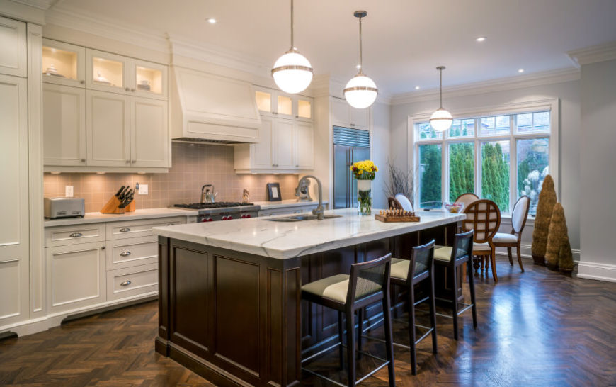 A large bay window filters in natural light to this stunning kitchen. The white marble countertops and cream colored cabinets pop against the dark wood of the island and floor.