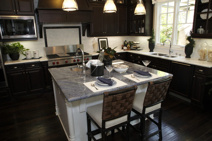 This kitchen features an almost black wooden flooring and cabinets. The dark colors make the white and grey marble countertops shimmer in the sun.