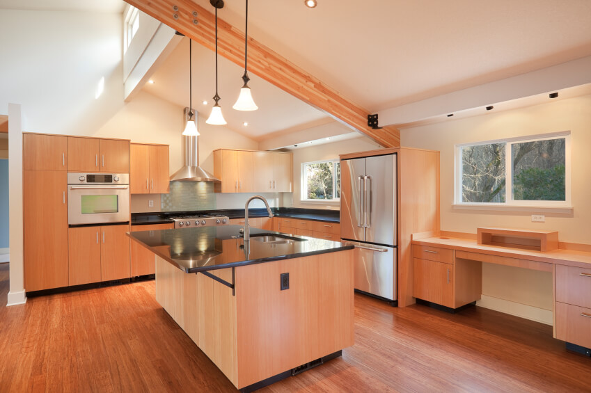 This bright kitchen utilizes the angled ceiling to add interest, while the countertops and warm wood floor add weight and help to ground this airy space.
