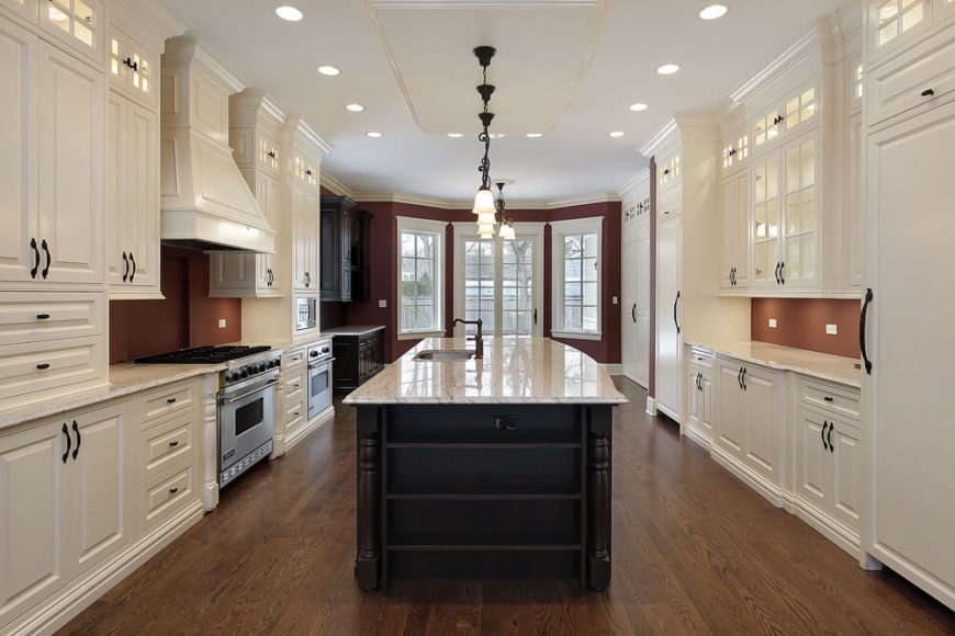 This lengthy, enormous kitchen wraps full height white cabinetry around an expanse of rich natural hardwood flooring. A dark stained island commands the center, topped with white marble.