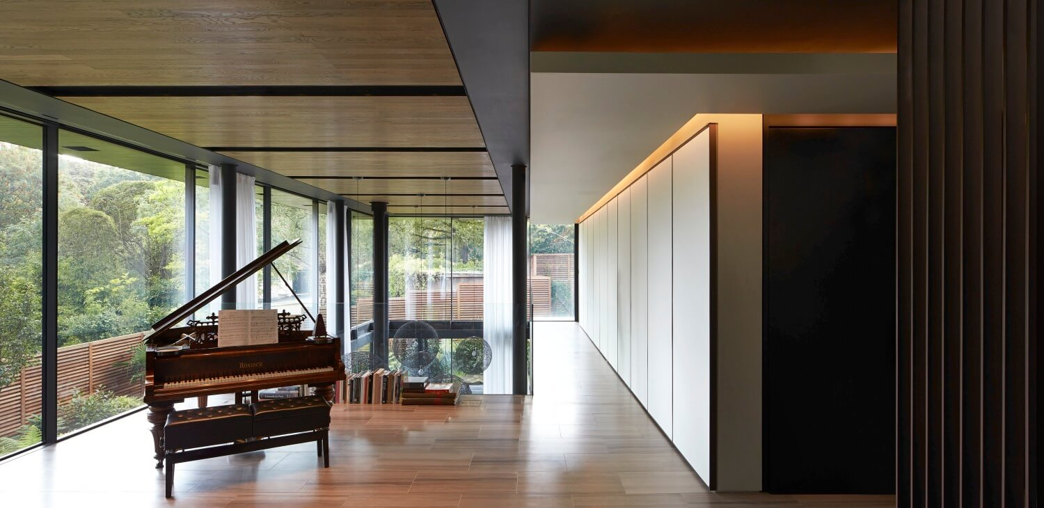 "The upper floor continues into this minimalist ""study"" space, with a small library of books leaning against the glass railing behind a grand piano. The panoramic views afforded on this floor are unrivaled."