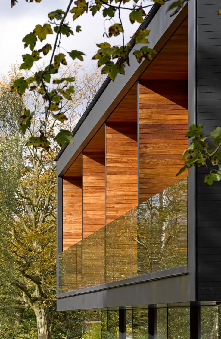 The cantilevered upper floor houses a segmented balcony with rich hardwood panels top to bottom.