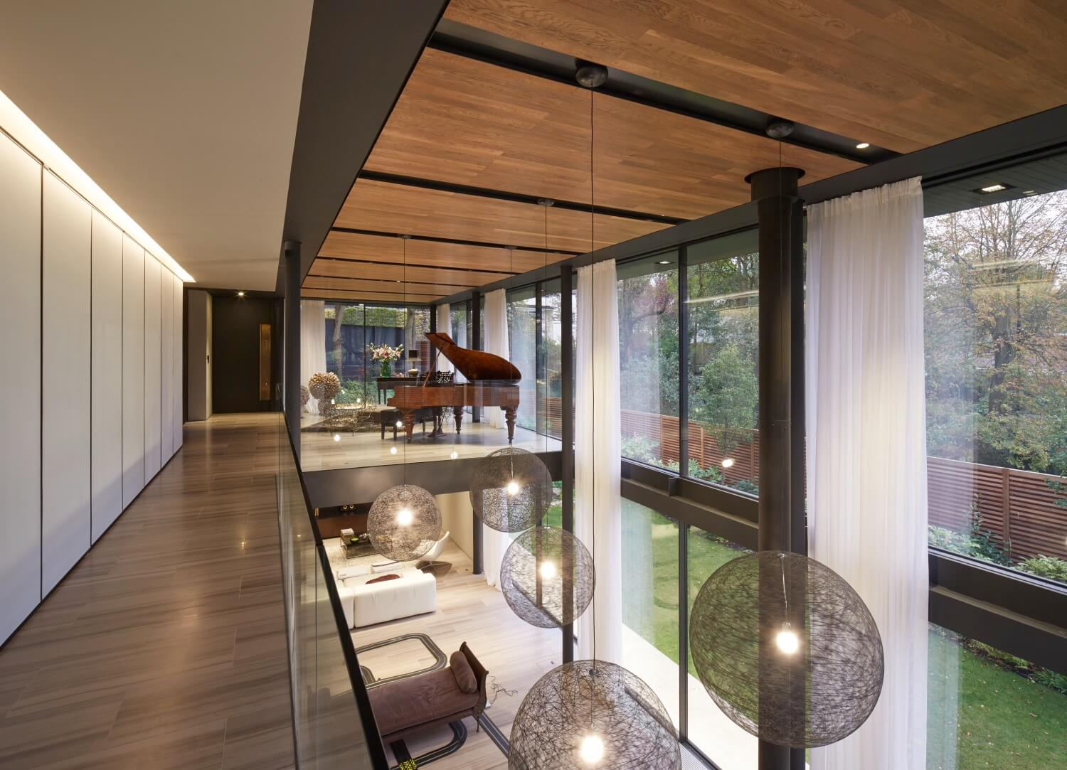 Here's the upper floor view of the massive living room below and smaller area above, holding a grand piano in full view of the surrounding woods.