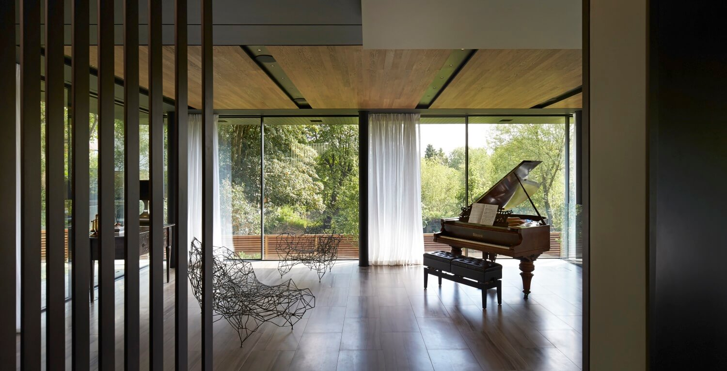 The minimalist space features a pair of avant-garde wireframe chairs and small traditional wooden desk, in addition to the classical piano.