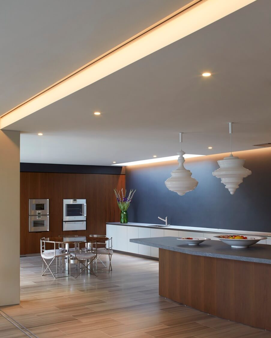 The lower level open-plan space includes this Zen-like kitchen, with a mixture of rich wood tones and sleek modern touches. Large island at right supplements the lengthy minimalist countertop.