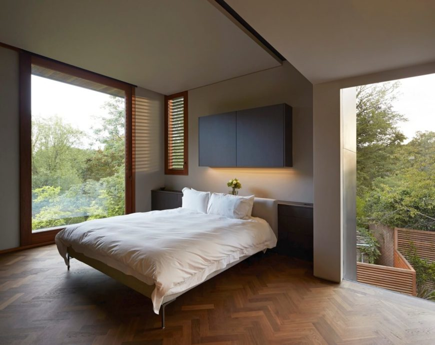 Contemporary master bedroom features built-in storage and hardwood flooring with herringbone pattern.