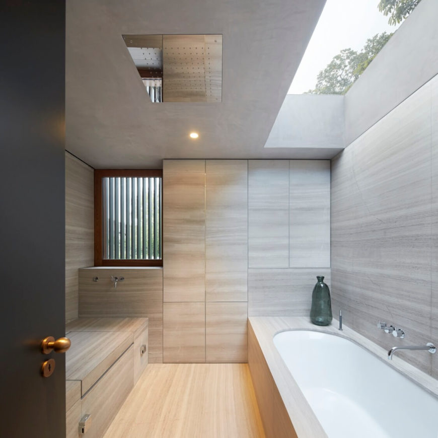Cozy master bathroom surrounded with light hardwood walls, flooring and built-in storage. Natural light streams through the skylight above the bathtub.