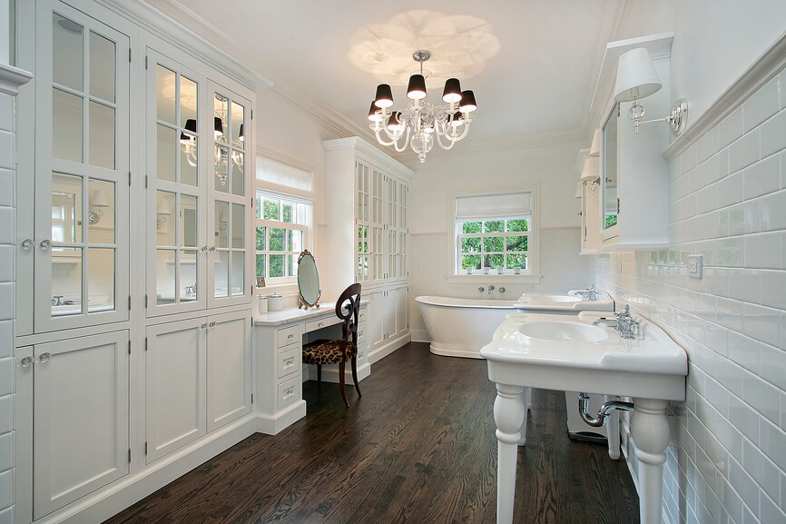 This lengthy white bathroom features rich, dark hardwood flooring for a striking, high contrast look. A pair of porcelain vanities stand along the right wall, clad in white tile, while full height cabinetry with glass doors fills the left wall. Pedestal tub can be seen at the far end.