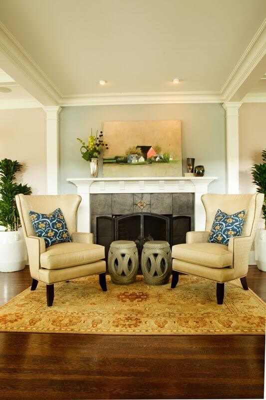 The small seating area in front of the beautiful fireplace has two wingback chairs and drum-shaped side tables. The beautiful pastoral piece of original artwork above the fireplace gives the space a sense of gentle serenity.