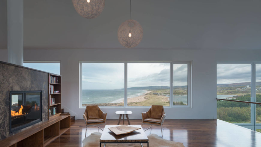 A view of the living room from the left side, past the matching chairs and through the window. The view of the two bodies of water mixing is a fantastic sight.