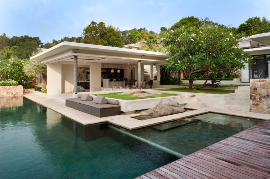 A small modular storage sofa sits by the edge of the infinity pool, with decorative boulders behind and to the right. The entirety of this courtyard is detailed to be an oasis.