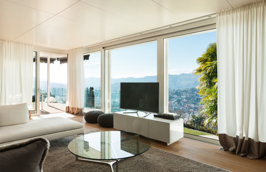 Billowy white curtains are thick enough to fully obscure and maintain the privacy of the occupants when they are pulled to cover the massive seamless windows.