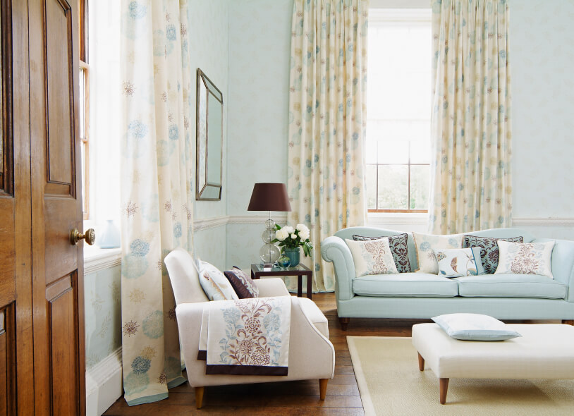 Great Light Blue Living Room With Patterned Curtains.