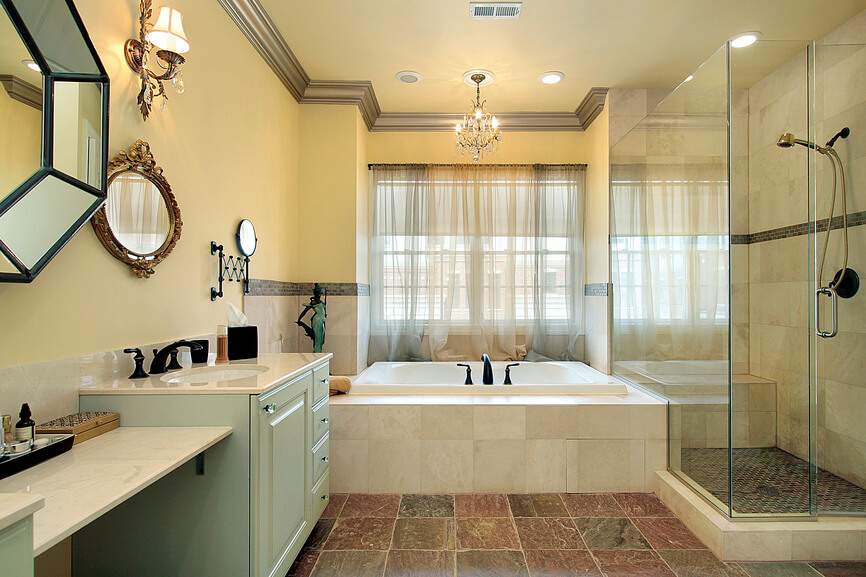 This master bathroom features rich, earth-toned tile flooring, with dark shades of red and green, uniting a space filled with marble and soft yellow tones. All-glass shower enclosure at right hugs the large soaking tub, while a dual vanity at left sports soft green painted cabinetry.