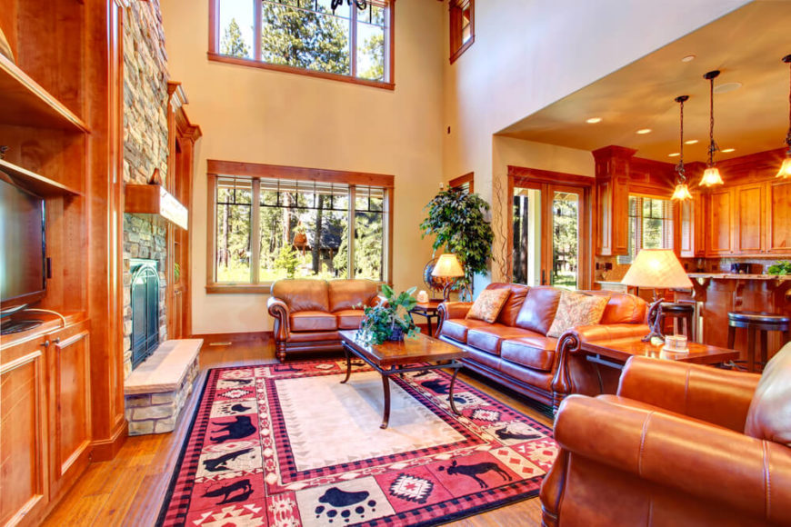 A grand room with a cabin-themed area rug and a set of leather seating arranged around a coffee table in front of a screened stone fireplace. This room has two matching wrought iron and wood end tables that complement the design of the centered coffee table. While these end tables don't have any storage, they are a perfect place to set a glass while watching television, and are a perfect spot to place the branch-like lamps.