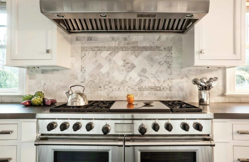 A closer look at the cooking range and double ovens. The backsplash is in a beautiful white and gray tile with a square of smaller tiles creating a different pattern than the rest of the backsplash.