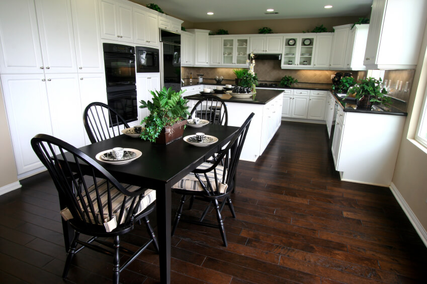 This Sprawling Kitchen Sets Pristine White Cabinetry Over Rich Warm Toned Hardwood Flooring While Dark Floors
