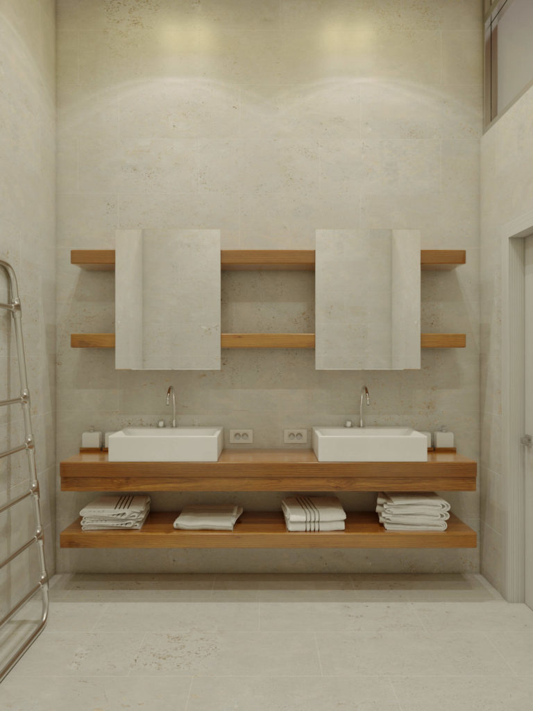 The dual vanity is mounted upon a set of wall-mounted floating wood panels, with a pair of vessel sinks below frameless mirrors.