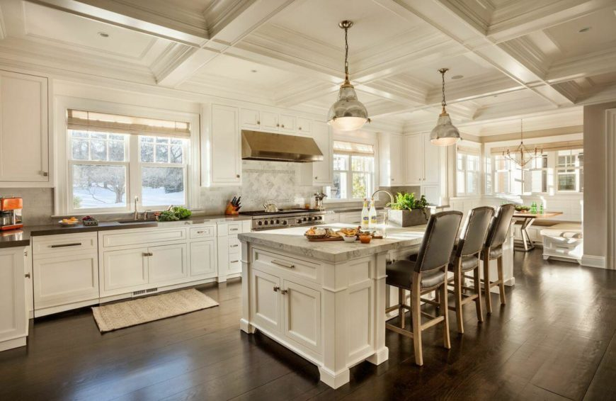 A look from the opposite side of the kitchen at the extensive cabinetry and the lovely breakfast nook that's surrounded by windows.