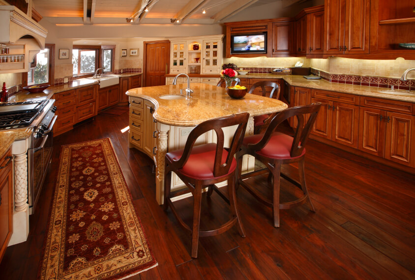 Deep rich hues in this dark wooden flooring creates a beautiful contrast with the light countertops. This huge kitchen is simply divine with the color contrasts all over the room.