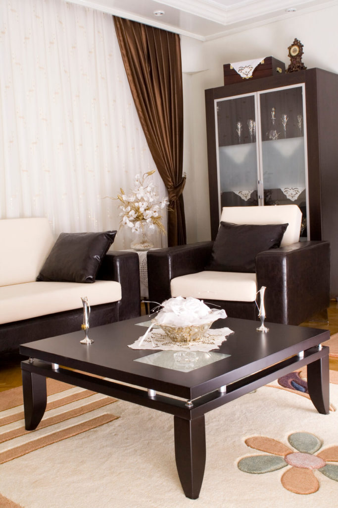 Rich satin curtains are paired with sleek leather seating and a contemporary dark wood coffee table. Elegant, almost feminine, accents are scattered throughout the space.