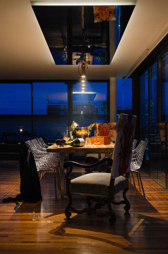 The dining room at night sparkles in the overhead light. The stainless steel ceiling above the table is less noticeable at night.