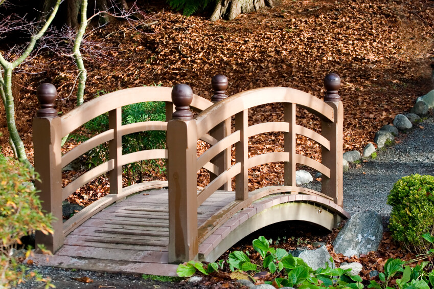 This is an example of a small garden bridge in wood. Rather than bridging the expanse over a water feature, this structure crosses a small natural ditch.