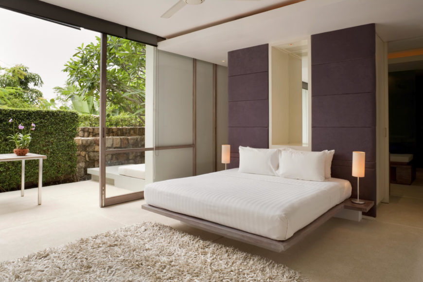 The master bedroom has a sliding door that leads out into a courtyard with stone walls and hedges. This room faces the interior of the island, rather than the water.