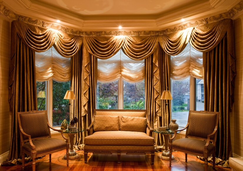 This incredibly luxurious and ornate living room has equally ornate drapes. The shades are also fabric and are gathered at the center in an immensely attractive way.