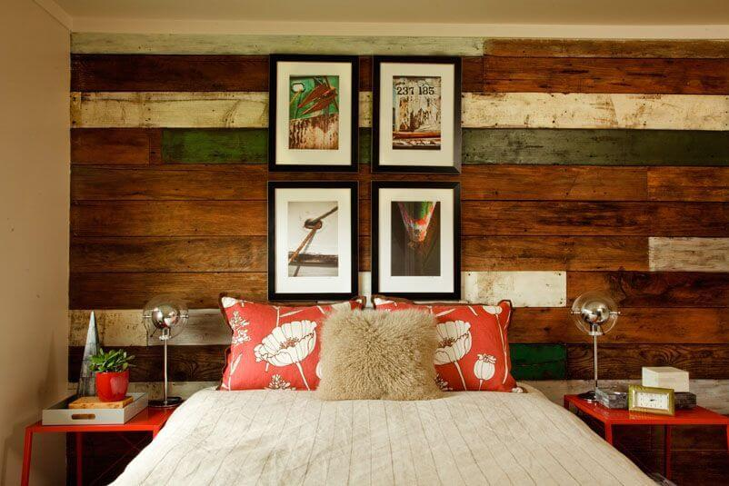 A beautiful bedroom with a wooden accent wall behind the bed and a mixture of textures in the bedding. Four photographs above the bed add length to the bed.
