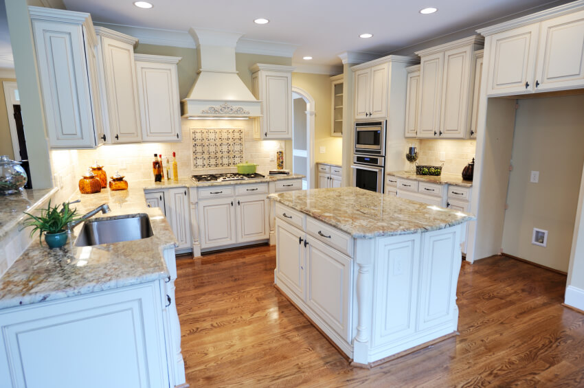 This Kitchen Is Particularly Inviting With Intricate White Cabinetry And Light Granite Countertops Over Rich