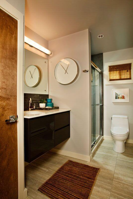 One of the bathrooms in the home has a dark vanity with a single sink basin and a glass shower stall.