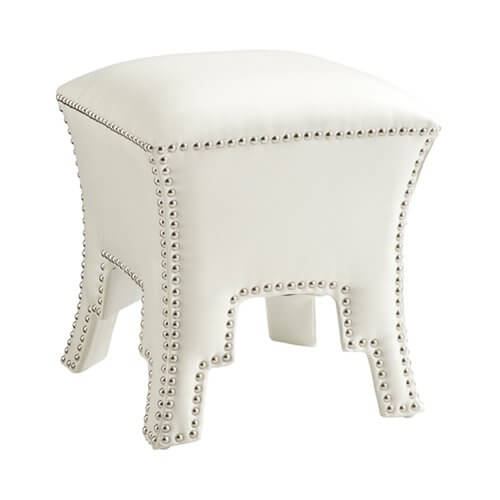 An ottoman with a rounded, cushioned top and a cut-out base design. A chromed nailhead trim adds depth of texture to this leather piece.