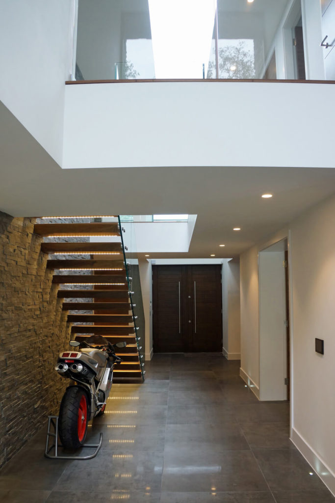 This hallway is illuminated with recessed lighting and strip lights from the floating staircase where a parked motorcycle is displayed.